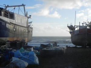 Two fishing boats are on the beach at Hastings; the sea can be seen in the background