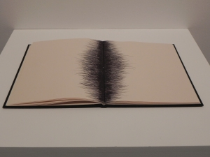An open artist's notepad on which biro marks have been made across the crease of the pages