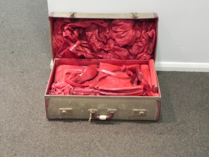A suitcase is open showing the possessions inside which are all painted red