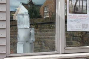A stack of three ice blocks reflected in the window of the Lynchpin Gallery in Eastbourne